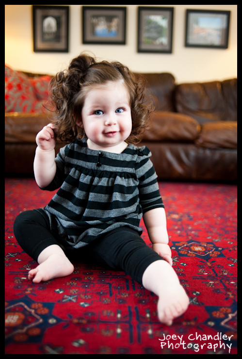 Baby girl playing with hair in front of a couch - San Francisco Baby Photographer