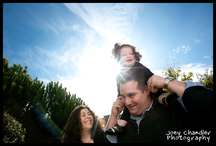BAby girl on Dad's shoulders with a sun flare - San Francisco Baby Photographer