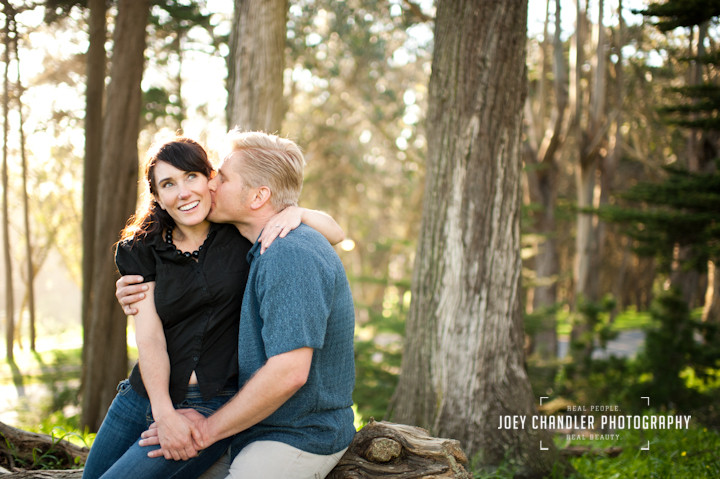 Man kissing his fiance in woods near the Lyon St Stairs - San Francisco engagement and wedding photographer Joey Chandler