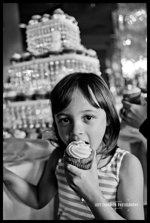 girl eating cupcake in front of cupcake tower at San Francisco wedding reception