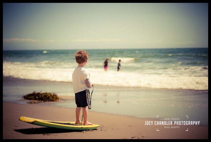 Boy standing on boggie board at the beach in Capitola