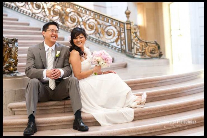 Bride and groom sitting in rotunda at San Francisco City Hall