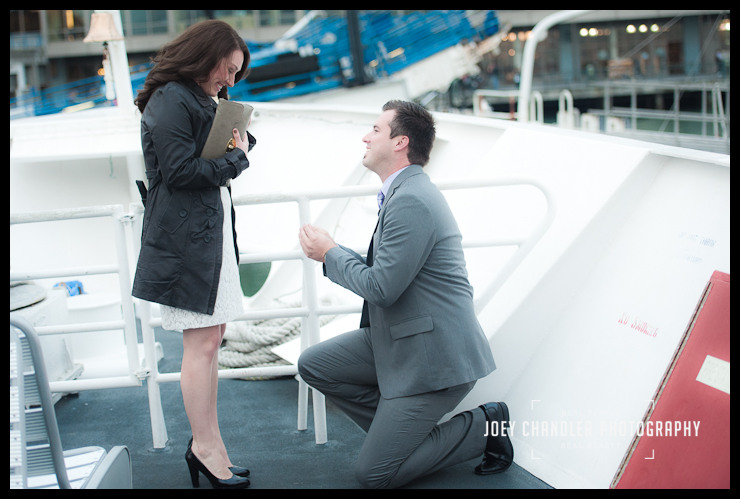 Man on one knee on the deck of a San Francisco ferry boat with a ring in his hand, looking up at a woman who has a look of surprise and excitement on her face.