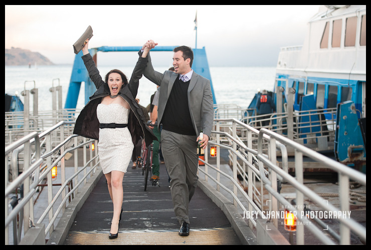 Walking down the gangplank of a ferry boat, a newly-engaged woman raises her arms in celebration with a look of excitement on her face, as her fiance looks on.