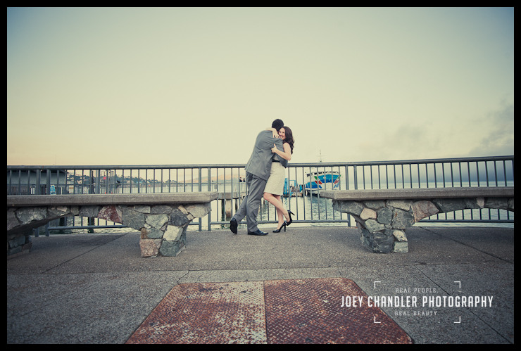 With the San Francisco bay as a backdrop, a newly engaged couple hugs.