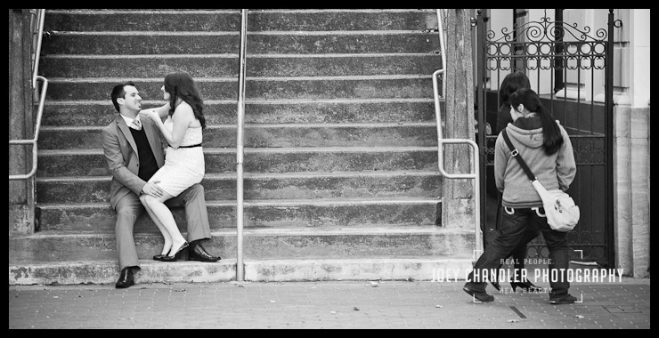 Black and white photo of a newly engaged couple sitting on cement steps- she is sitting on his knee and he is lookking at her and smiling adoringly.
