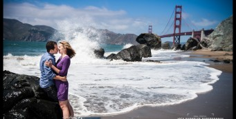 Engaged couple kissing in the sea spray at Marshall Beach in San Francisco
