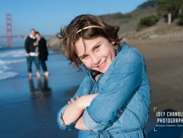 Girl smiling with family in Baker Beach in San Francisco